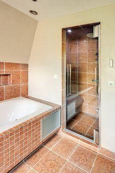 Deze landelijke wellness badkamer met Toscaanse uitstraling is voorzien van een Cleopatra stoomcabine met lichttherapie en op maat gemaakte badkamermeubels van Custom Made De Jong. Een badkamer om volledig tot rust te komen.