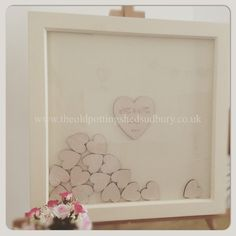 Drop top wedding guest book. Cream frame with a cream card back. Natural wooden hearts for your guests to sign. Order your guest book from us at www.theoldpottingshedsudbury.co.uk