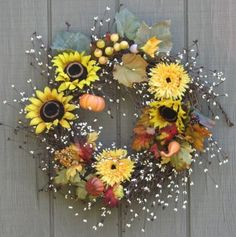 I love the delicate grapevine with berries, sunflowers, mums and miniature pumpkins in this wreath.  Etsy.
