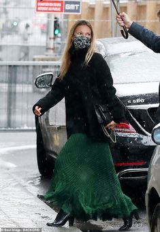 Beauty: Dressed in a floor-length British racing green skirt, a black coat and face mask, ...