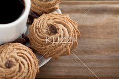 cropped image of cookies and beans in saucer. - Cropped shot of cookies with coffee beans and coffee cup in saucer on wooden plank in a macro image.