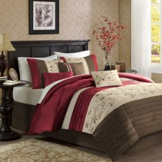 <p>With a lustrous dupioni fabric that catches the light, this duvet cover set features an embroidered floral pattern that separates the rich red and chocolate brown sections.