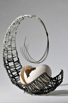 Lesley RIsby  I followed the link and it says ceramics.  I can see that for the shell, but am intrigued how it applies to the wire part.  There appears to be something on the wire.  Wish I could learn more.  UPDATE:  just found her site.  Here's the page where she describes her art: http://www.lesleyrisby.co.uk/page3.htm