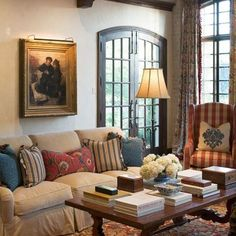 Love all of this....the black trim on the French doors, the slipcovered couch and colorful pillows, curtains, art, rug, tons of books