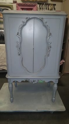vintage radio cabinet turned storge cabinet. Painted a soft gray with detail glazing.