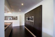 Moderne keuken met ingebouwde kast met inbouwapparatuur. Eiken donker gelakt gecombineerd met een eiken licht gelakt kookeiland. Gemaakt door Geert Bouten Interieur op maat