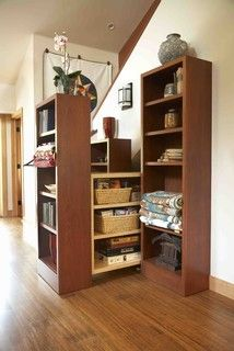 Use the space under the stair for storage. Pantry style pull out shelving allows access behind standard depth bookcases.Staging by Karen Salveson, Miss