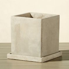 Shop concrete pot with saucer.   Heavy-duty cement block roots plants in industrial fashion.  Crafted with a drainage hole, planter rests on accompanying tray with raised border to catch excess water.