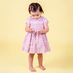 This is a lovely pink on pink ditzy print dress for a classic beauty. It has an adorable rounded collar and gently puffed short sleeves. The bodice is hand smocked and the dress comes with a pair of matching ruffled hem bloomers.