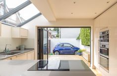 Modern side kitchen extension | lean-to | residential property | Lewes | floor to ceiling units | bi-fold doors | sloped aluminium glass roof | halogen hob | car park courtyard