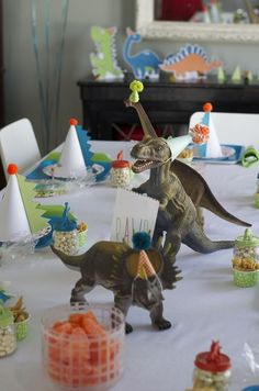 Adorable dinosaur party: mini party hats on dinosaurs, spikes on party hats, dinosaur food (bugles as dino claws, chocolate rocks, jelly beans(?) as dinosaur eggs).