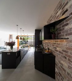 Glossy black kitchen cabinets coupled with exposed brick wall to create textural…