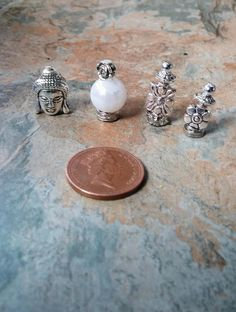A stunning pair of miniture silver perfume bottles, a while perfume bottle with silver details and a Buddahs head statue. A lovely addition to your fairy garden dollhouse or that of a friend or loved one.  Thank you for your time. | Shop this product here: http://spreesy.com/SpryHandcrafted/105 | Shop all of our products at http://spreesy.com/SpryHandcrafted    | Pinterest selling powered by Spreesy.com