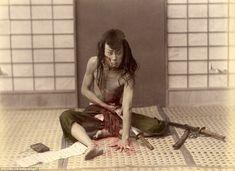 A Samurai warrior appears to commit Seppuku or Harakiri in Japan - the ritual of taking one's life through disembowelment