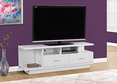 """Complete your home decor with the simple contemporary elegance of this chic white TV console. With ample surface area that can accommodate up to a 60"""" flat panel TV this piece will add style and functionality to any living room. Featuring 2 large storage drawers for DVDs, CDs or other AV accessories and 4 open concept shelves perfect for your electronic components this unit is sure to keep you organized in style. Sleek silver colored drawer handles finish off the modern look that makes t..."""