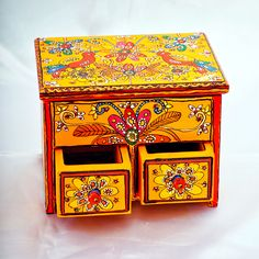 Unique en son genre, cette boîte de couleur orange avec 2 tiroirs, 4 compartiments et couvercle à rabattement, éclate par ses tonalités très indiennes.
