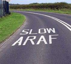 Welsh language - Bilingual road markings near Cardiff Airport. In official Welsh-speaking areas, the Welsh signage appears first. Where Is Wales, Funny Street Signs, All Road Signs, Welsh Names, Trunk Road, Welsh Language, Road Markings, Welsh English, Humor