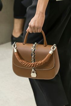 Nacido como cartera para la escuela, este bolso se reinventa pero conserva sus rasgos tradicionales: líneas rígidas y  silueta cuadrada.