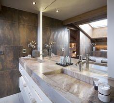 Luxueuse salle de bains, avec très grand miroir, double vasque en marbre clair, carrelages cuivrés...