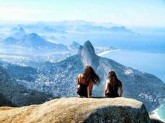 BRAZIL – Rio de Janeiro. The two girls are sitting at the highest point of Pedra da Gávea mountain. In front of them is Morro Dois Irmãos (Two Brothers Hill) and below on the left of it is the Rocinha favela, the largest slum residence in Brazil. https://www.google.ca/maps/place/Pedra+da+G%C3%A1vea/@-22.9870621,-43.2881937,13z/data=!4m5!3m4!1s0x9bd6d13e950037:0x2c49dc1b12837f3f!8m2!3d-22.9975707!4d-43.2848892