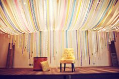 As 'ribbon walls' go this one is by far the most interesting. I think this bride took pieces of material and cut them into strips as opposed to using ribbon and then made a canopy above the ceremony space. This brings a great ambiance to the room but also draws the eye from the back to the front of the space.    (Wedding Arch Ideas)