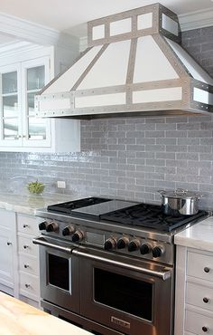 Andrew Howard interior Design: Fantastic white and gray kitchen with white cabinets paired with marble countertops and ...