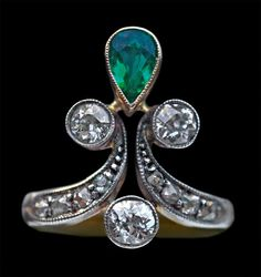 BELLE EPOQUE Ring Gold, silver, emerald & diamond Length: 1.8 cm (0.7 in) European, c.1900 Tear drop emerald of good colour 0.75 cts approx 3 Victorian cut diamonds 0.6 cts approx 8 Victorian cut diamonds 0.25 cts approx An ideal engagement ring