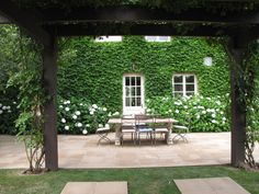 Love the blooming hydrangeas. Pergola covered with roses and ornamental grape. Beds of hydrangeas along the house wall and boston ivy cover the house (Designer Paul Bangay)