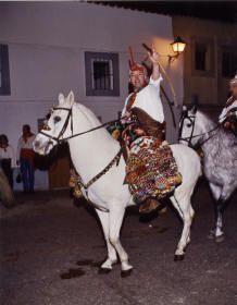 Un Sanantonero peleño hace el recorrido de La Encamisá con su caballo adornado con la manta típica de madroños y el pañuelo multicolor terminado en pico en la cabeza.