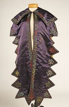 Pelerine, circa 1830, British, purple silk with intricate floral embroidery. Interesting evolution of the term 'pelerine' when this looks rather like a mantle, or evening shawl. Pelerines by the mid 1800s were small shoulder coverings fashioned to match a dress and came to a point or sharp pair at about the midriff. This is a beautiful garment, and I wonder what decade the owner stopped wearing it. In storage at the Met.
