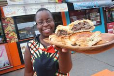 Evis Chirowamhangu holds up a tray of Mnandi meat pies inspired by her childhood in Zimbabwe featuring her bestseller steak and onion at the Scadding Court shipping container food market.