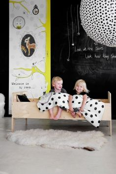 Biała podłoga i czarna ściana z farby tablicowej w pokoiku dziecięcym - idealne połączenie. Żółte dodatki świetnie ocieplają wnętrze, jak i łóżko z jasnego drewna:)