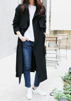 A white t-shirt is paired with a black trench coat, jeans, and white sneakers