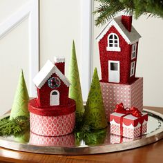 "Create a Tiny Village Display : Tiny wrapped boxes provide a base to a few glittering paper houses that take up very little space. To make ""trees,"" wrap squares of scrapbook paper into cones and glue the edges; cut off the bottoms to be level. For extra sparkle, place the grouping on a silver tray. :: totally wanna do this one this year. :] christmas villages are so much fun. ♥"