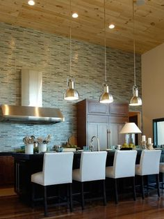 .recessed lighting with light wood ceiling, stainless steel accessories and that whole wall of color... i love it.