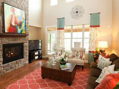 An inviting conversation area is created with a chocolate brown couch and two white chairs in this transitional living room. Tall window treatments accentuate the two-story ceilings and a contemporary red rug grounds the space with a pop of color. Coral Living Rooms, Grey And Brown Living Room, Living Room Decor Brown Couch, Living Room Turquoise, Living Room Red, Living Room Colors, Living Spaces, Chocolate Brown Couch, Transitional Living Rooms