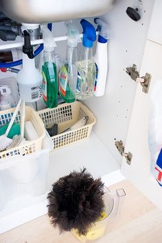 Inserting a tension rod into a cabinet and hanging bottles from it can help to free up space in a cleaning cabinet.
