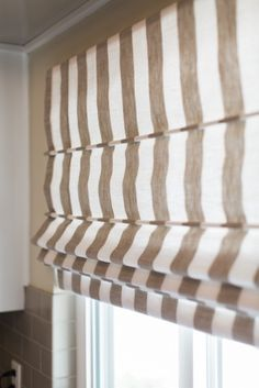 Taupe and cream linen striped flat fronted custom roman shades for the kitchen window.