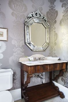 Elegant powder room features walls clad in gray and silver damask wallpaper lined with a Venetian vanity mirror over a warm stained rippled washstand with shelf topped with white marble.