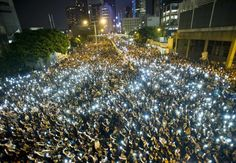 """""""Protestors and student demonstrators hold up their CELL PHONES in a show of solidarity during a protest outside Hong Kong's Legislative Council on Sept. 29."""""""
