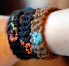 Knit Bracelet, Pattern: cast on 4 stitches, knit back and forth until it's the right length for your wrist, bind off. make a loop at the end – this is the button hole. use the tail at the other end to sew on the button. use a contrasting color yarn, or embroidery thread, to personalize your bracelet – just stitch a little something. weave in the ends.