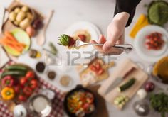vegetarian table hands: Chef in the kitchen holding a fork with spaghetti, tomato sauce and basil, food ingredients and utensils  Stock Photo