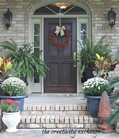 Astounding Red Wreath On Black Wooden Main Door With Double Small Windowed Also Cool Black Antique Fixture Wall Lights Outdoor Decor Views And Awesome Green Plant And Flowers Veranda Decor As Inspiring Front Porch Furniture With Brick Exposed Wall Patio Vintage House Designs
