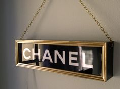 This wooden light box is modelled on a vintage Chanel light box of the type used in department stores. Hand crafted using a combination of stencils and hand painting. It transforms any room with a beautiful warm light. The Sign can be hung from the chain like the famous hand bag, hooked on the wall or placed on a shelf to add instant Chanel glamour. It measures 53cm x 15cm x 9cm depth.