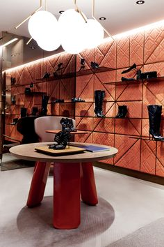 Typical elements of this concept are the metal suspended grids that gives spatial illusion, the wooden boiseries with bronzed glass shelves and the luxury area for limited edition products. And for the first time a laboratory where a shoemaker will work shoes in front of the clients.