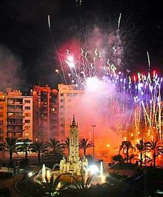 """SPAIN / Celebrations - Bonfires of San Juan (Alicante). The festivities officially begin on 20 June with the """"plantà"""", or building of enormous bonfires with their tongue-in-cheek cardboard figures which fill the streets of Alicante with wit and good humour. That day the """"barracas"""" or large tents are also put up to serve as a public dance floor, and where fiesta-goers can sample the typical figs and """"cocas"""""""