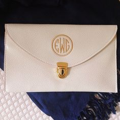 Cream/ivory vegan leather envelope clutch purse monogrammed in gold with a framed, round design.