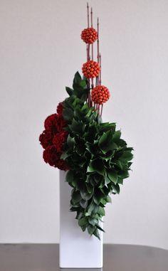 Ruscus, Celosia, Cornus alba, Smilax glabra. Modern, vertical floral design arrangement.