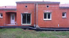 Un chantier où l'on retrouve une porte d'entrée PVC, des baies vitrées coulissantes à deux vantaux, deux rails, des fenêtres PVC à deux ouvrants.