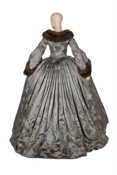 The blue brocade dressing gown designed by Gilbert Adrian and worn by Norma Shearer as Marie Antoinette in Marie Antoinette (1938). The original blue dressing gown is being shown with a pink corset and petticoat based on the original costume, along with a cross necklace also inspired by the original costume piece. [source: Julien's Live]